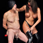 Busty long-haired mistress in a red mask and high boots dominating her poor slave in a mask and with a penis clamp