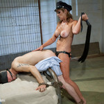 Cruel mistress in sexy black outfit whipping her slave boy while fucking him with strapon.