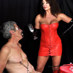 Poor old fart with clamps and a weight on his nipples gets punished by his busty mistress in a red latex dress and boots when forced to drink his own
