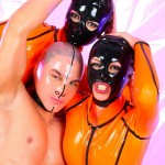 Two black haired flexible sexbabes in orange latex posing with their muscular guy