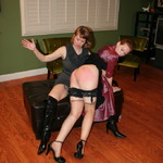 Gorgeous redhead gets her booty spanked by a randy brunette.